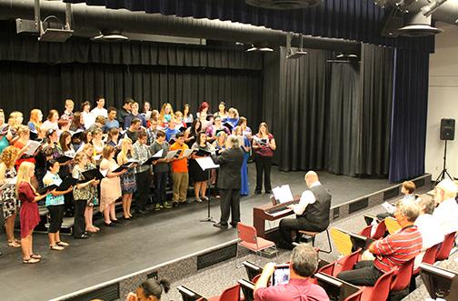 Dr. Gregory Turner, music instructor at Fort Scott Community College,  conducts the Scarlett Crossroads choir on Friday, Oct. 4, in the  Allen Theater. About 40 high school students from four area schools  -- Iola, Altoona-Midway, St. Paul, and Uniontown -- practiced during  the day for auditions to the Kansas Music Educators Association honor  choir. They were joined in the public concert by members of the Allen  Community College Concert Choir. Accompanying the group is Ted Clous,  Allen music instructor who coordinated the event.
