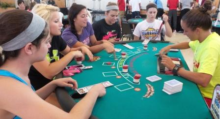 Rachel Janzen, right, a residence hall director and assistant women's basketball coach, deals to students playing blackjack during Casino Night.