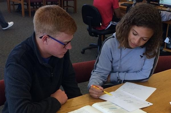 Michaela Trobough assists Wesley Leach with a math problem in the Academic Support area of the Allen Library.