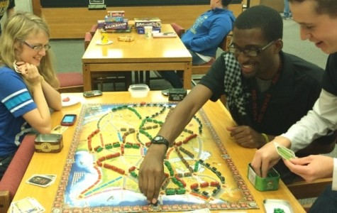 Meshach Adams makes a move playing Ticket to Ride as Kylie Gier and Nicholas Showalter look on.