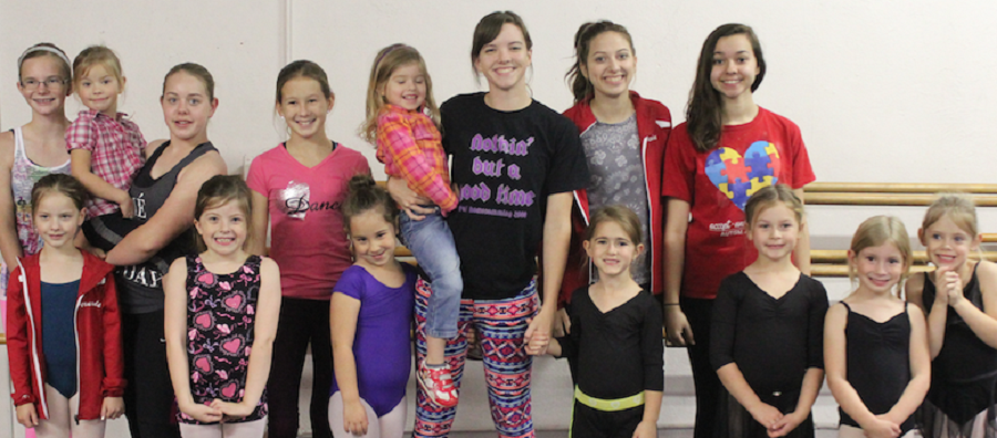 Chelsea Lea, holding a youngster in the back row, is standing with her tap dance students at Chelsea's Dance Academy.