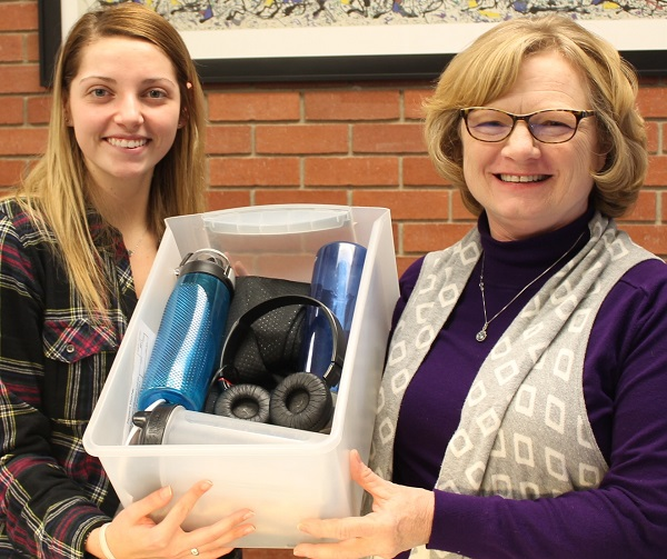 Hannah Hudlin, left, and Becky Leis show the contents of the lost and found box in the administration office.