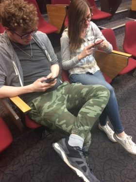 Freshman Austin Wickwire and Paige Durand scroll through their social media profiles while in the Allen Theater.