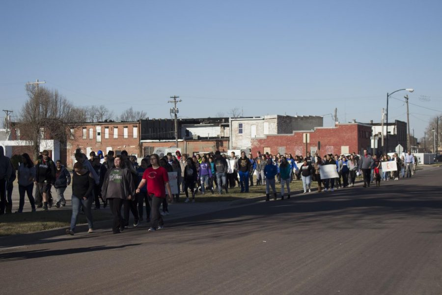 Iola High School students and faculty participate in the #ENOUGH: National School Walkout by walking around the Iola Square in support of safety in schools.