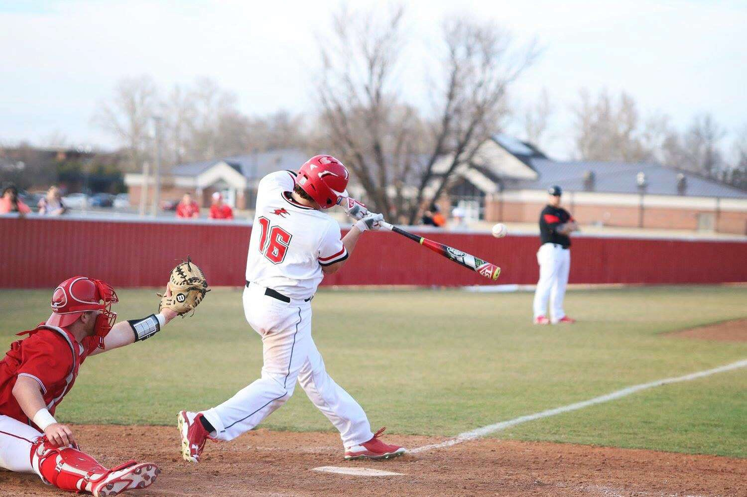 Sophomore Nathan Best makes contact with the baseball driving it down the third base line.