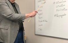 William Shirley stands at his white board as he presents the notes for the day's class.