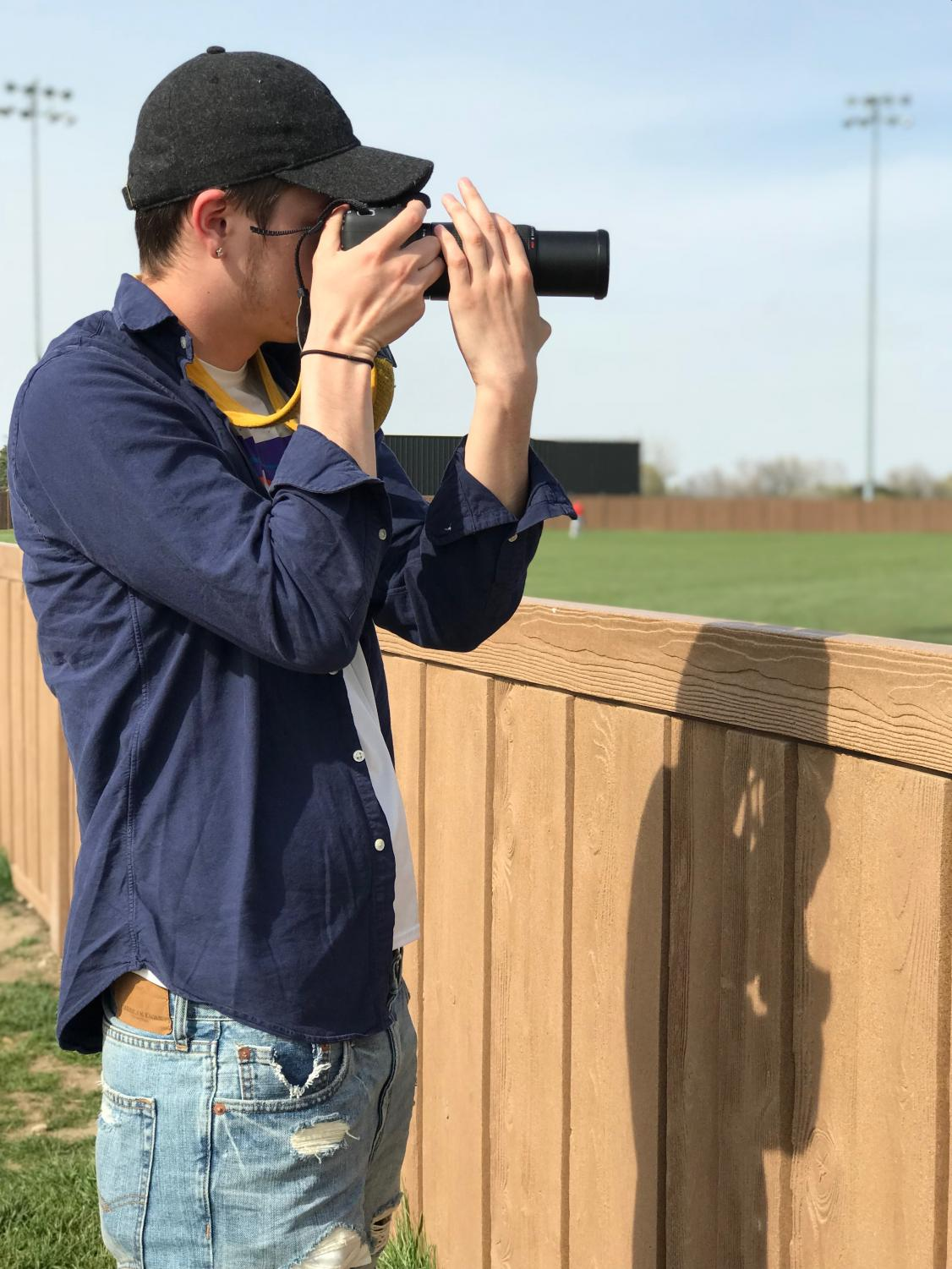 Student Life photographer Chase Hochard takes a photo of the Red Devil soccer team