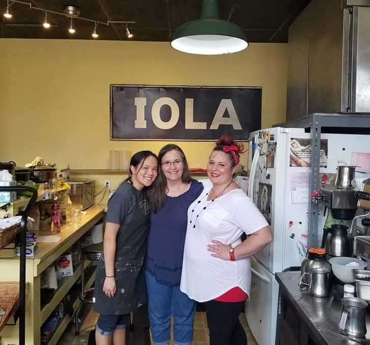 Sophomore Joie Whitney poses for a photo with Around the Corner owners Cindy Lucas and Jessica Qualls during her afternoon shift at the coffee shop in Iola, KS.