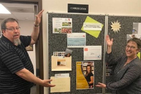 Bruce Symes and Terri Piazza try out their best Vanna White to display the Communications bulletin board in the Technology Building.