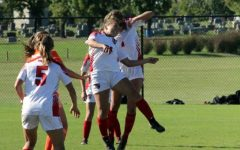 Members on the women's soccer team jump to keep control of the ball.