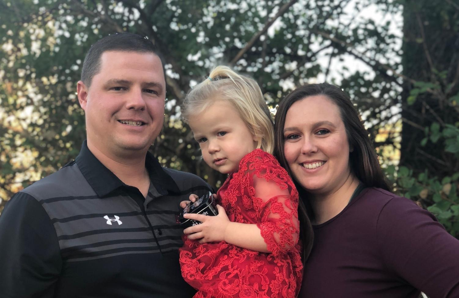 Andy and Whitney Shaw, both head coaches at Allen, pose with their two year old daughter, Tatum.