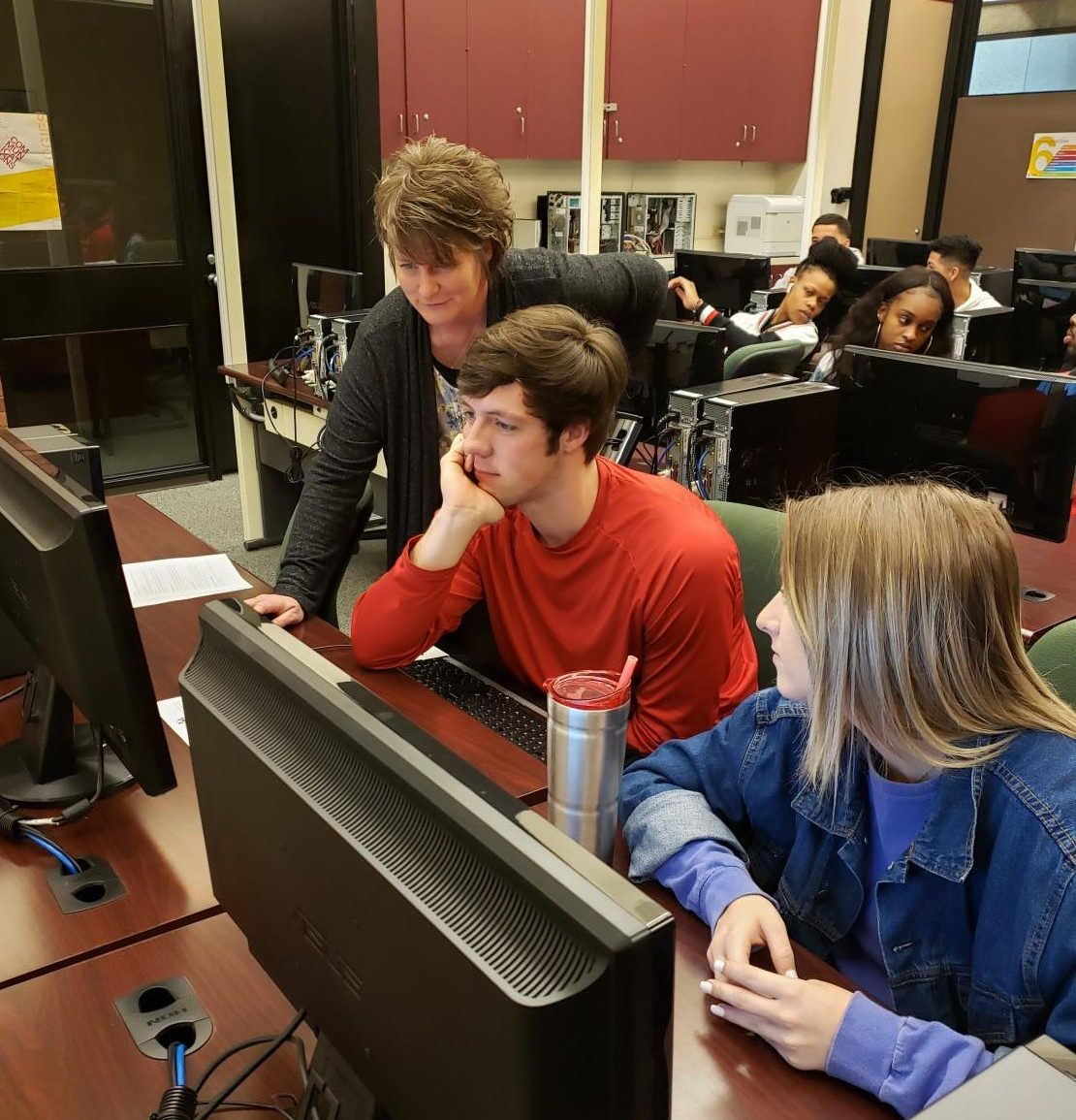 Business Instructor Nicci Denny assists students Brock Barkhurst and Emma Weseloh during the intro to business class at Allen Community College.