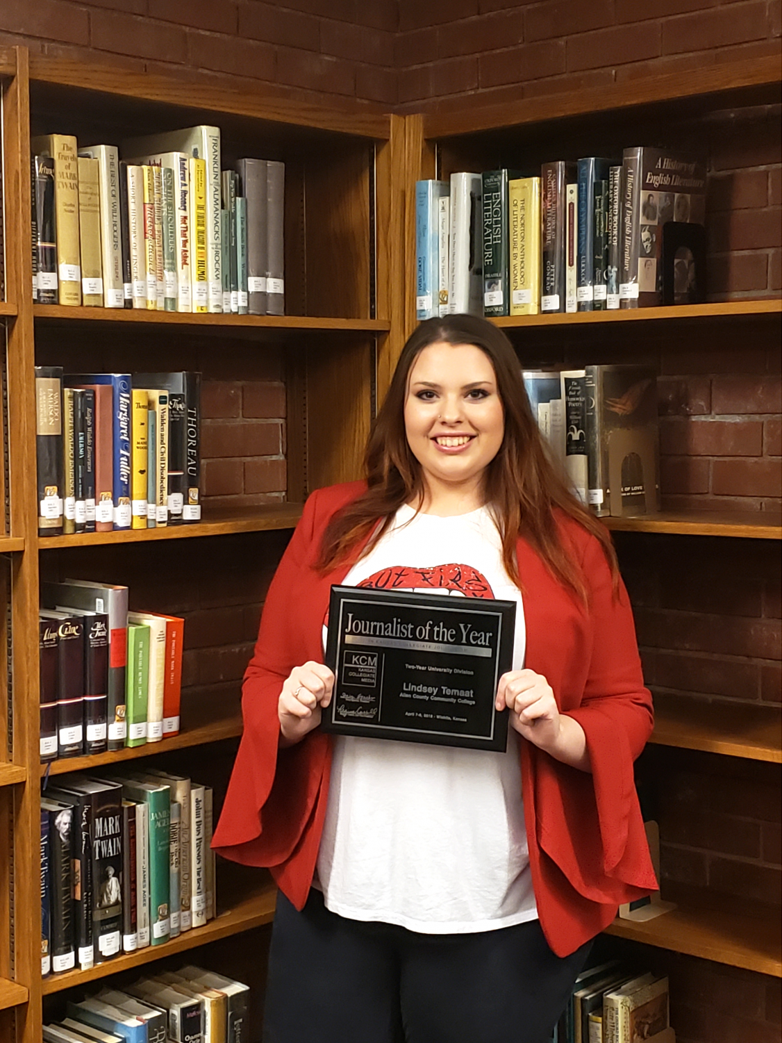 Lindsey Temaat smiles in the Allen Community College Library with her 2019 Journalist of the Year award.