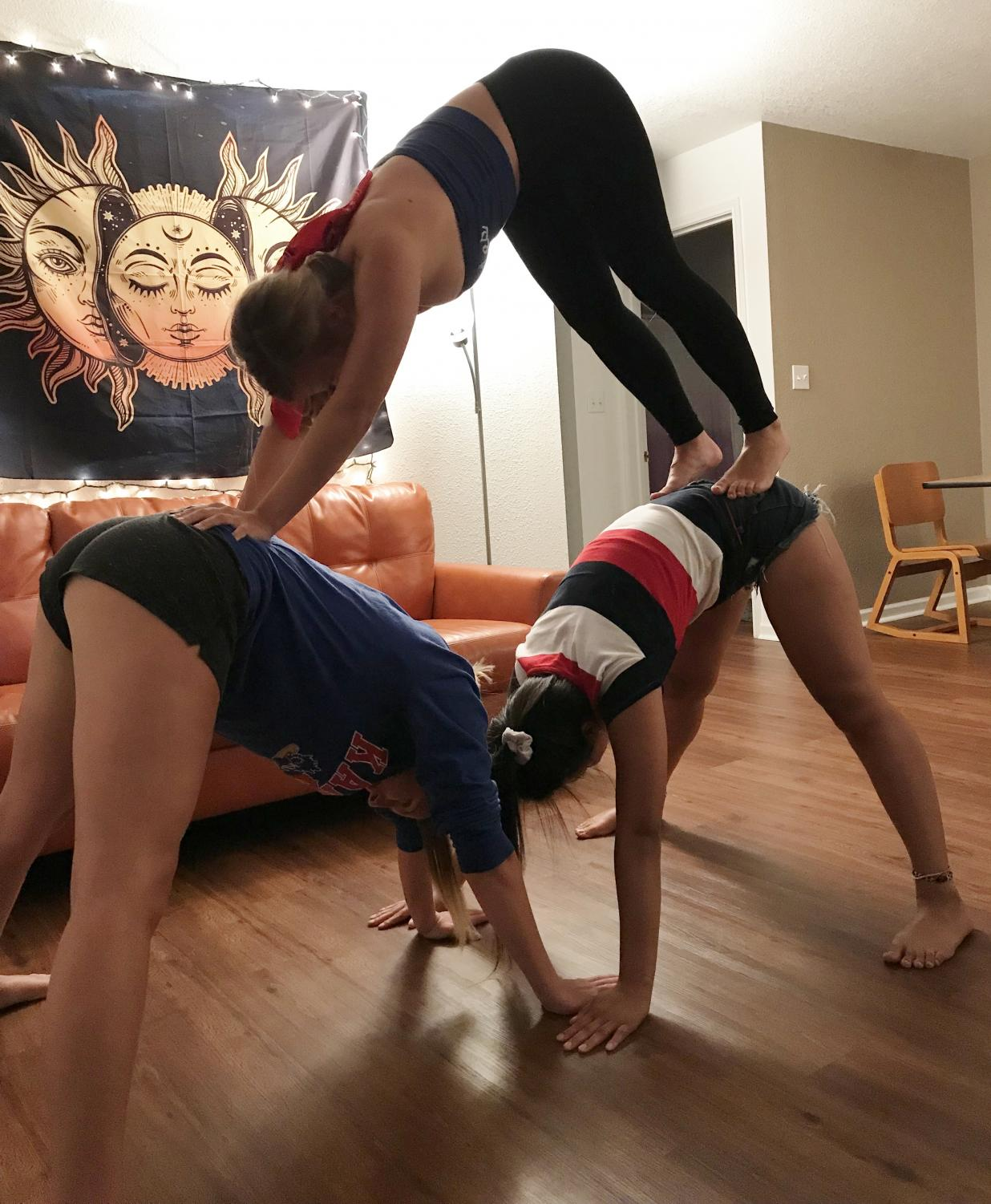 My roommates and I form a three-person pyramid yoga pose.