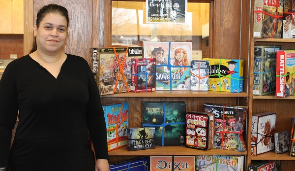 Heather Van Dyne, assistant library director, checks board games out to Allen students.